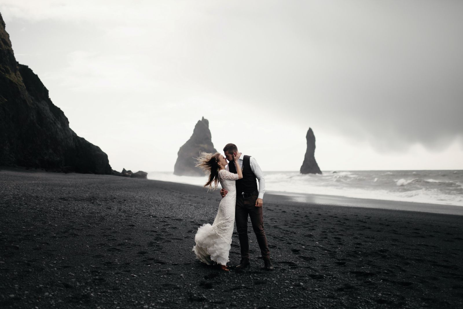 Couple kissing on a beach after an elopement wedding ceremony
