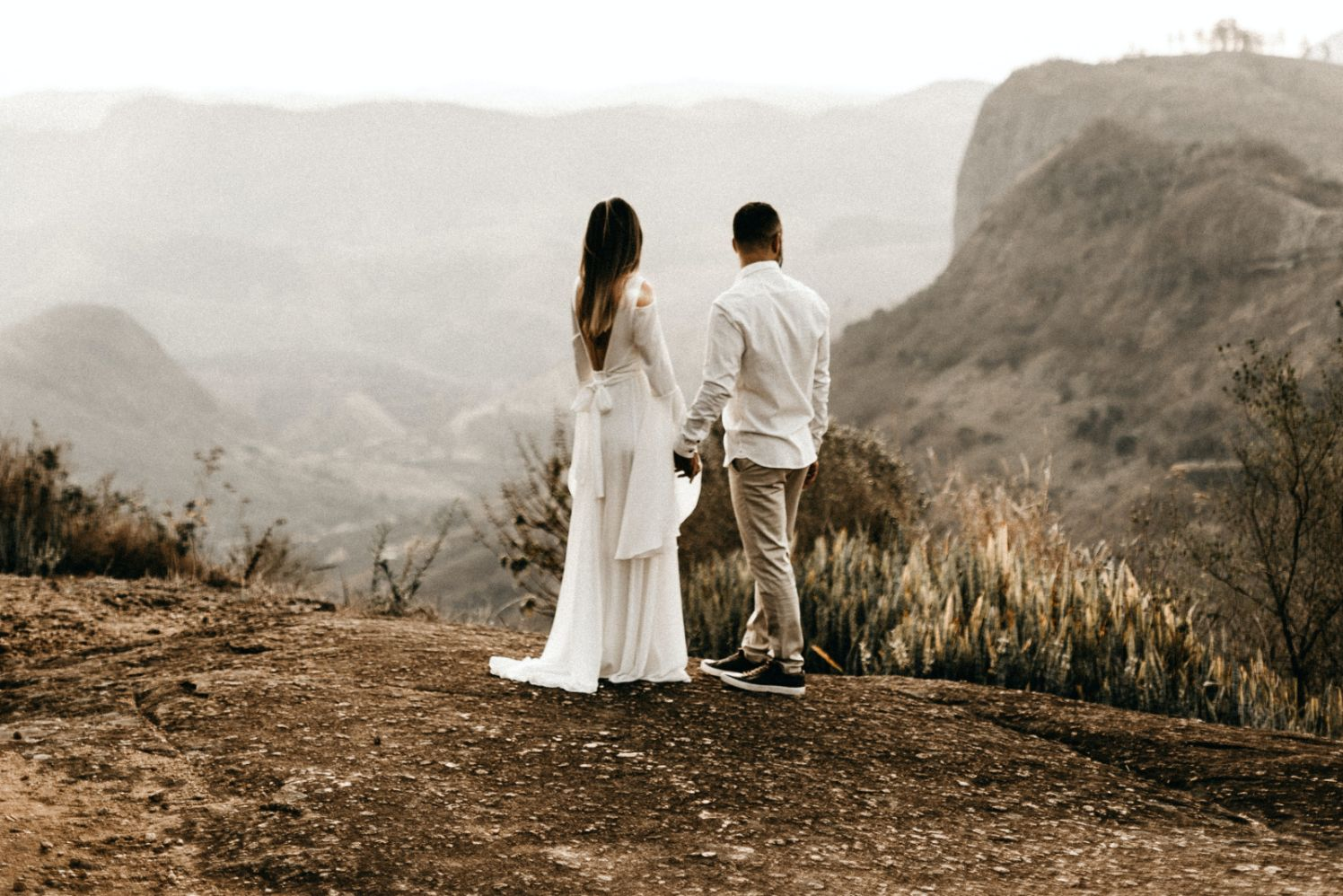 outdoor wedding elopement couple stood on top of a hill holding hands
