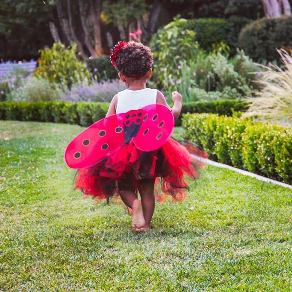 Little girl in ladybird costume running in a garden at a naming ceremony