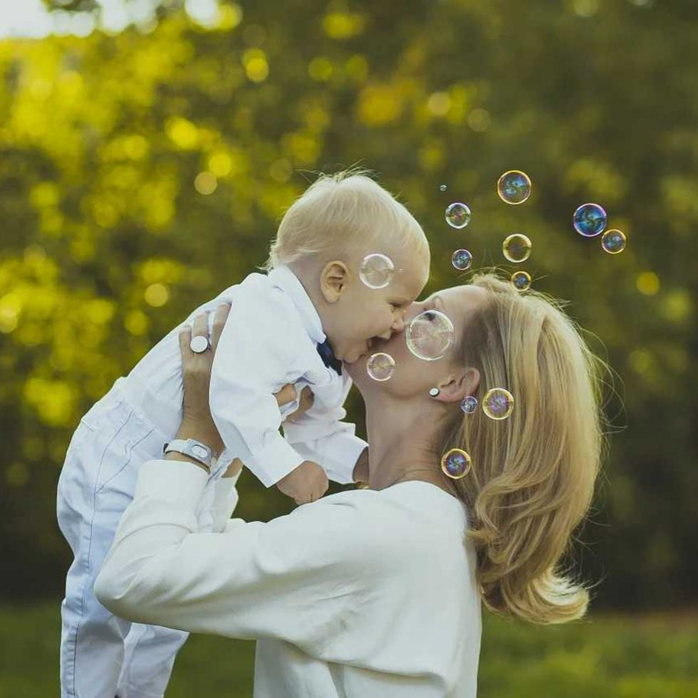 Mum kissing giggling son at an outdoor Naming Ceremony with bubbles being blown