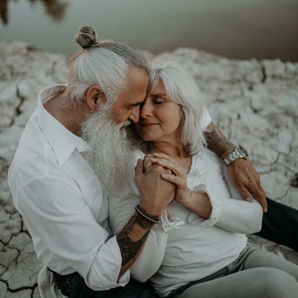 older man with long grey beard and tattoos cuddling his wife on rocks after vow renewal